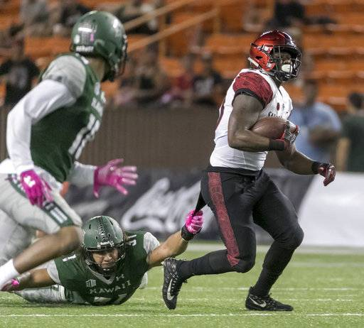 San Diego State running back Rashaad Penny (20) drags along Hawaii linebacker Jahlani Tavai (31) while running with the football in the second quarter of an NCAA college football game, Saturday, Oct. 28, 2017, in Honolulu. (AP Photo/Eugene Tanner)