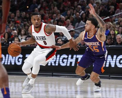 Portland Trail Blazers guard Damian Lillard, left, handles the ball as Phoenix Suns guard Mike James defends during the first half of an NBA basketball game in Portland, Ore., Saturday, Oct. 28, 2017. (AP Photo/Steve Dipaola)