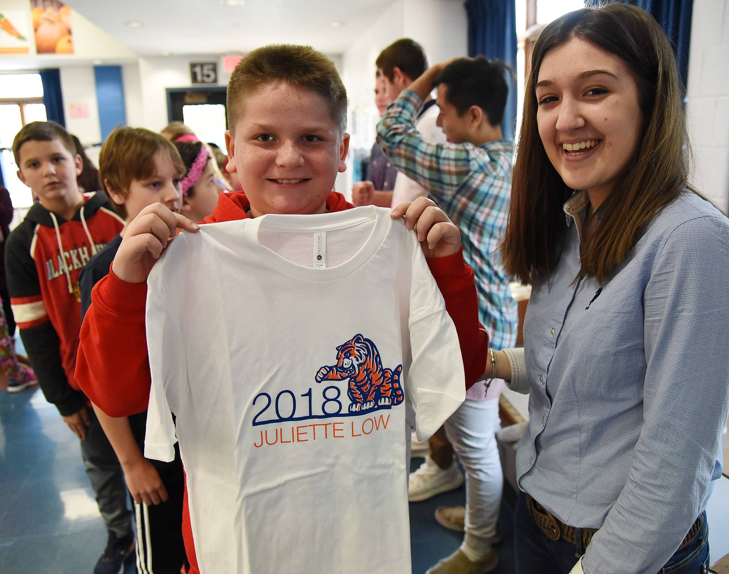 Alexander Villagrana holds up the T-shirt he just received from Rolling Meadows High School graphic design student Noel Manushi. Rolling Meadows students delivered T-shirts designed for the graduating fifth-graders at Juliette Low School as part of their graphic design startup company.