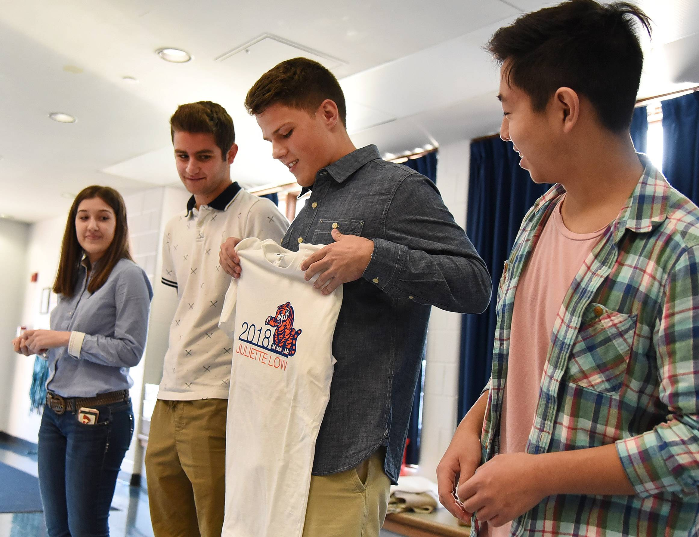 Rolling Meadows graphic design students, from left, Noel Manushi, Thomas Luedloff, Matt Lothery and Raymond Liu hold up one of the T-shirts they designed for the fifth-graders at Juliette Low School in Arlington Heights.