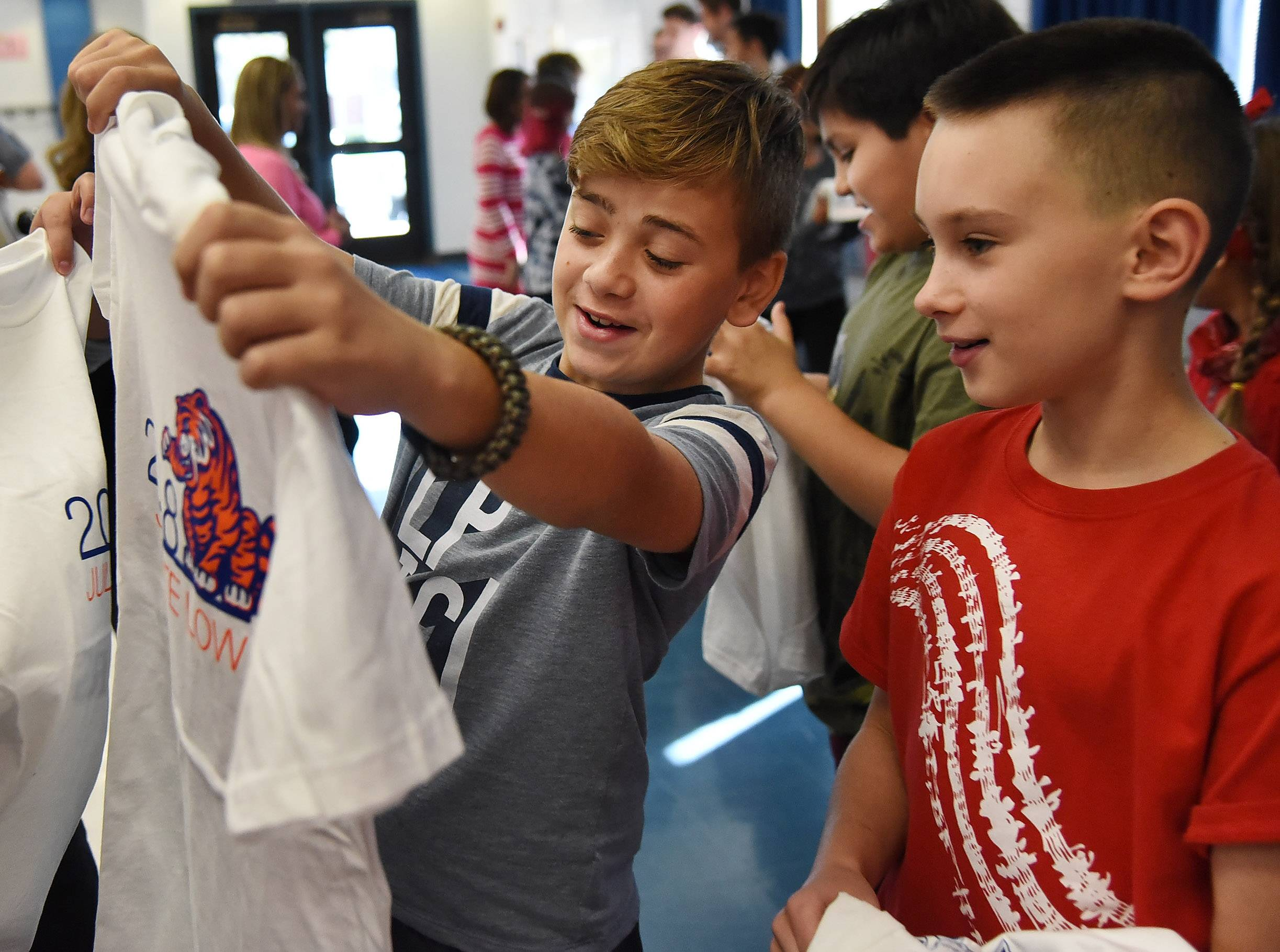 Juliette Low Elementary School fifth-graders Emi Stanev, left, and Max Pilat admire their new T-shirts, which were designed by Rolling Meadows High School students.