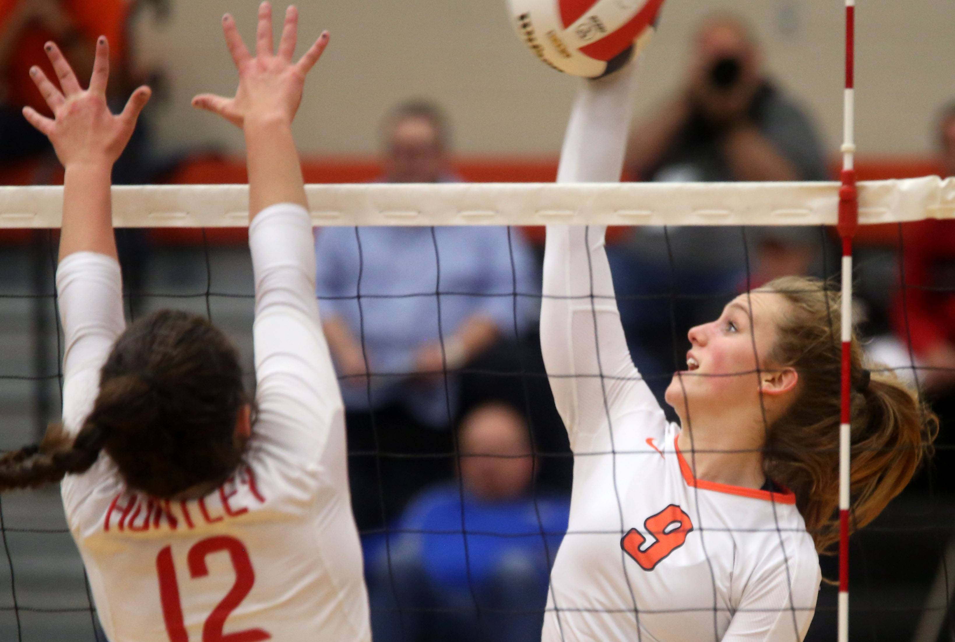 St. Charles East's Hannah Spicer, right, hits the ball as Huntley's Taylor Jakubowski blocks.