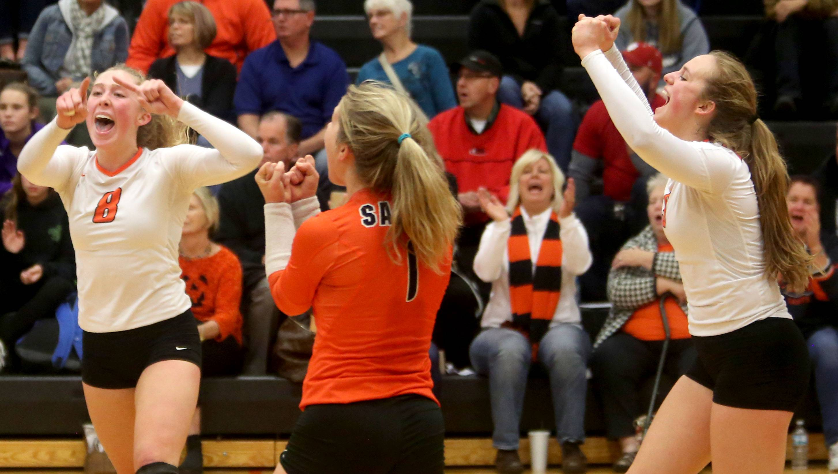 The St. Charles East Saints begin to celebrate a win over Huntley during sectional semifinal varsity volleyball action at Chuck Dayton Gymnasium on the campus of DeKalb High School Monday night.