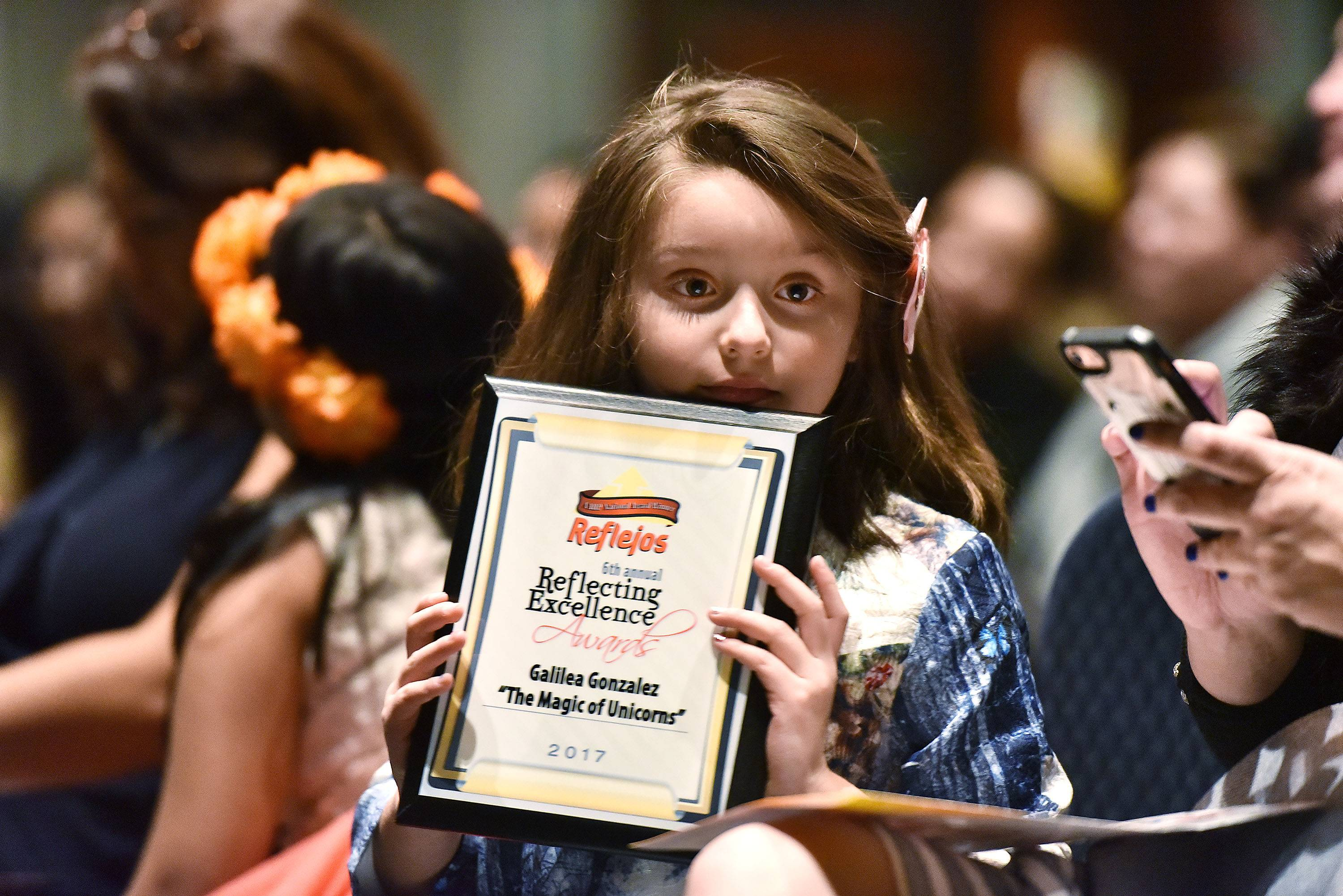 Galilea Gonzalez, 8, of Des Plaines, gets a round of applause Wednesday at Reflejos' Reflecting Excellence Awards at the Stonegate Conference and Banquet Centre in Hoffman Estates. She received a surprise award for her efforts to donate stuffed unicorns to children with cancer.