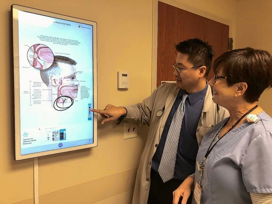 Dr. Andy Su, a radiation oncologist, and Mary Belville, an oncology nurse, review information to explain a diagnosis that is displayed on a touch-screen wall board installed by Outcome Health. The Nancy W. Knowles Cancer Center at Elmhurst Hospital is the first among dozens of Edward-Elmhurst Health locations in line to receive the wall boards and tablets throughout the next year.