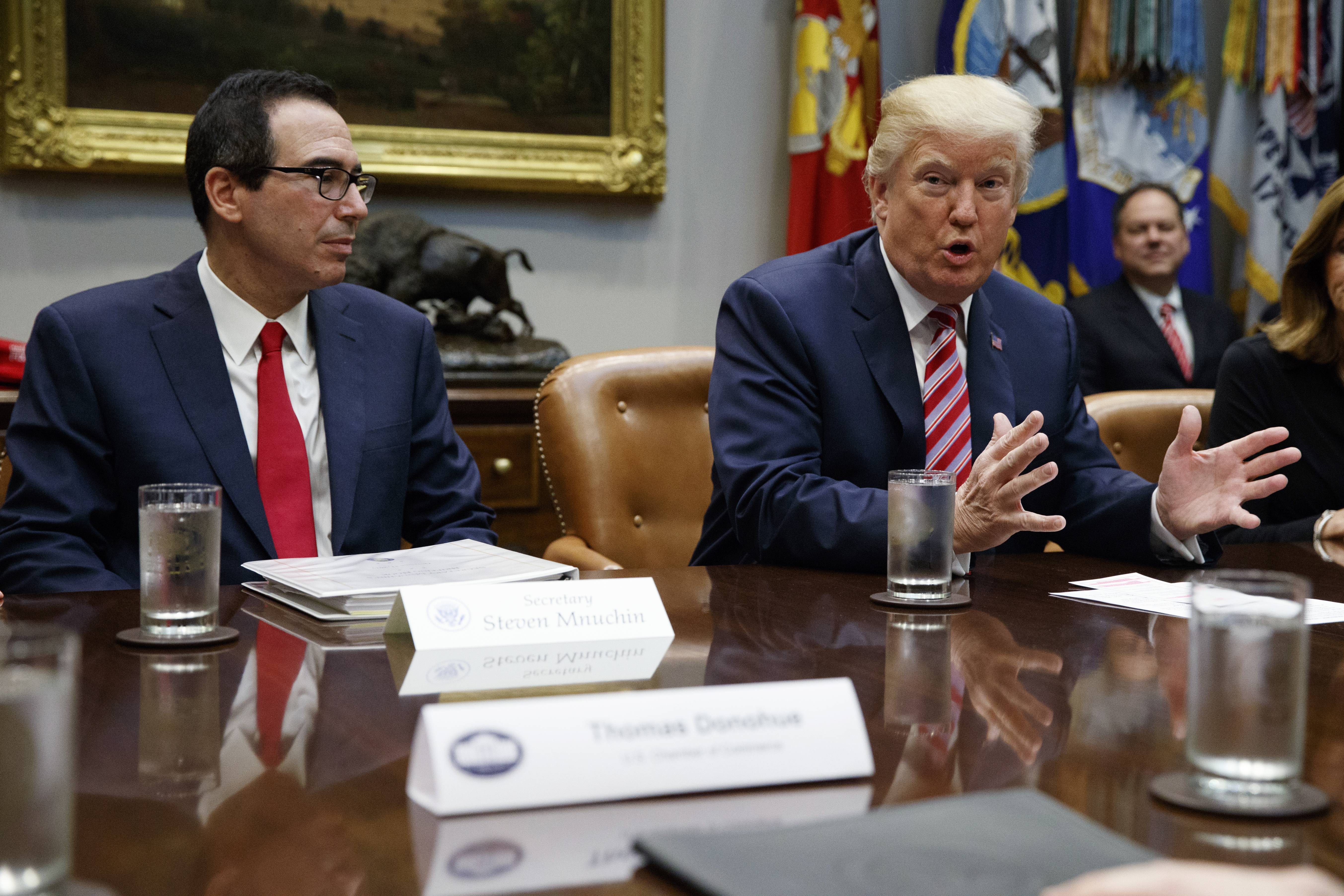 Treasury Secretary Steve Mnuchin listens Tuesday as President Donald Trump speaks during a meeting on tax policy with business leaders in the Roosevelt Room of the White House in Washington.