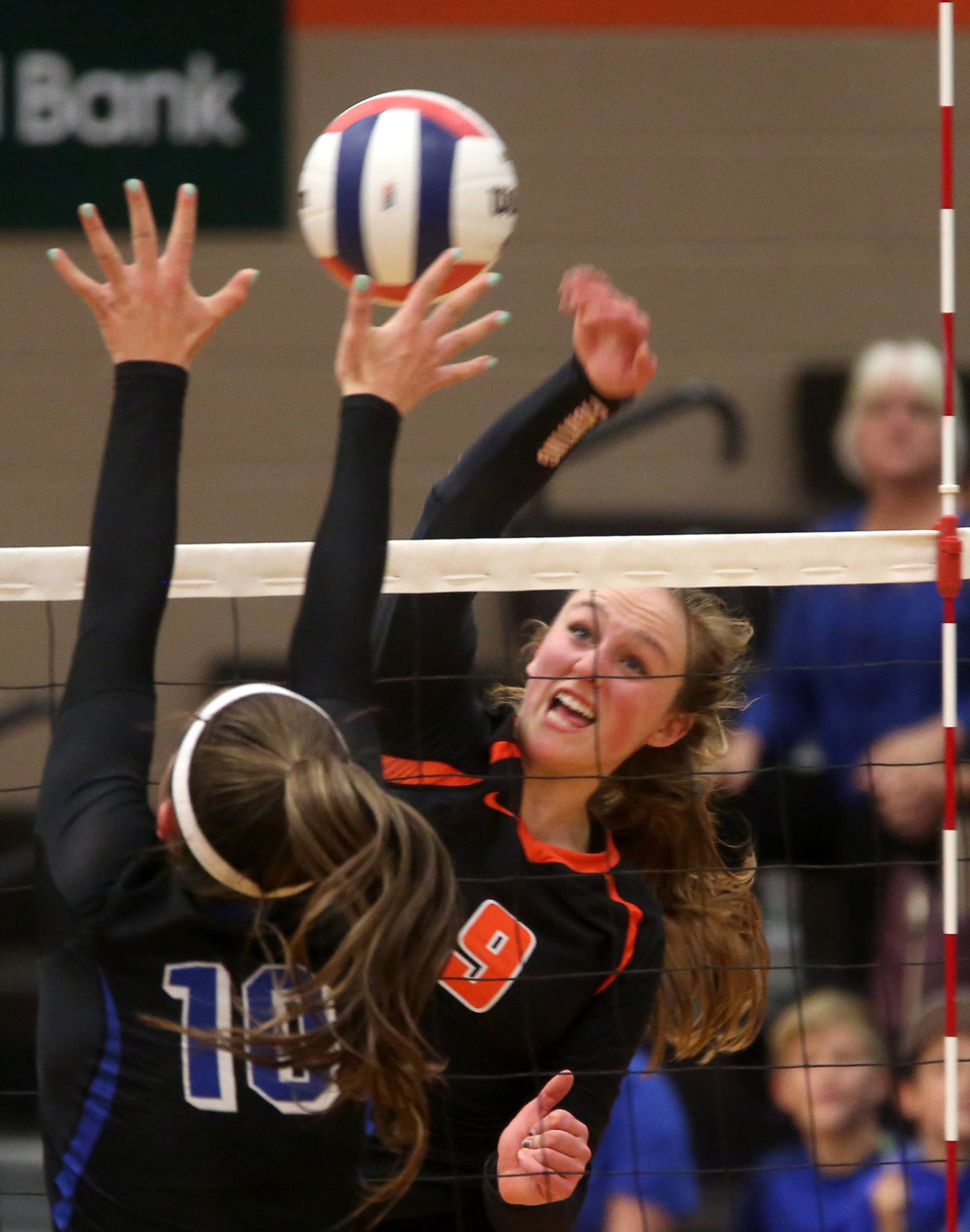 St. Charles North's  Amanda Parker, left, blocks as St. Charles East's Hannah Spicer slams the ball across the net during a Class 4A sectional title match at Chuck Dayton Gymnasium on the campus of DeKalb High School Wednesday night.