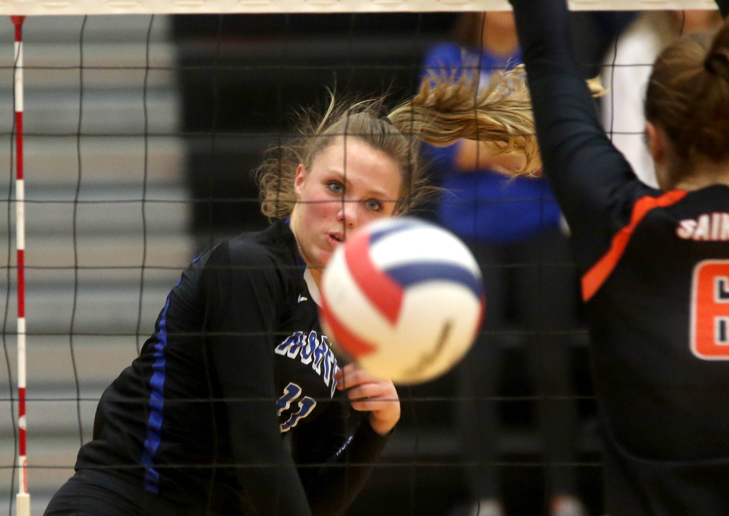 St. Charles North's  Katie Lanz slams the ball past St. Charles East's Klaudia Sowizral during a Class 4A sectional title match at Chuck Dayton Gymnasium on the campus of DeKalb High School Wednesday night.