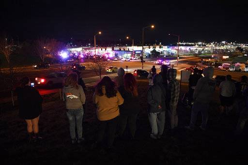 People stand across the street from a shooting investigation at a Walmart store, Wednesday, Nov. 1, 2017, in Thornton, Colo.  Several people were killed in a shooting inside a suburban Denver Walmart on Wednesday night, forcing customers to either hide in the store or frantically run for the doors. Thornton police advised people to stay away from the area as dozens of police cruisers and emergency vehicles raced to the scene. (Andy Cross/The Denver Post via AP)