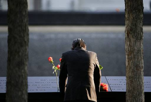 FILE--This Sept. 11, 2017, file photo shows a man standing at the edge of a waterfall pool at ground zero during a ceremony on the 16th anniversary of the 9/11 attacks in New York.  Since September 11, 2001, the neighborhood at the base of the World Trade Center has been transformed by new construction, and washed over by a wave of tourism. But this week's attack has reminded those who live, work, study and visit here of latent fears that this neighborhood would once again find itself in the crosshairs.
