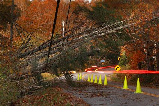A car leaves a trail of light as it passes under power lines weighed down by toppled trees in Freeport, Maine, Tuesday, Oct. 31, 2017. Utility crews scrambled to restore power throughout New England on Tuesday, one day after a severe storm packing hurricane-force wind gusts and torrential rain.