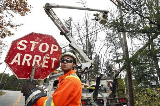 Canadian lineman Noah Clowater holds a bilingual stop sign while directing traffic while his coworkers restore power, Wednesday, Nov. 1, 2017, in Yarmouth, Maine. The New Brunswick, Canada, crew were among the hundreds of line and tree workers from as far away as Illinois, Kentucky, Ohio and West Virginia that have come to Maine following Monday's storm that knocked out power to nearly two-thirds of the state.