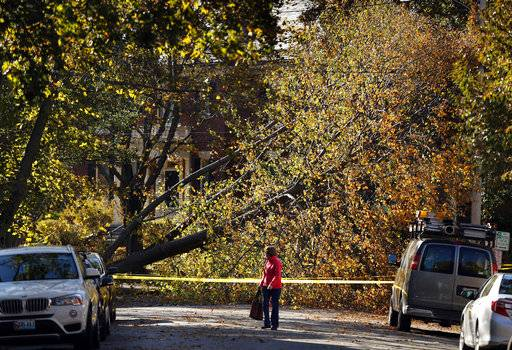 A woman walks down a street blocked by a storm-toppled tree, Maine, Tuesday, Oct. 31, 2017, in Portland, Maine. Utility crews scrambled to restore power throughout New England on Tuesday, one day after a severe storm packing hurricane-force wind gusts and torrential rain.