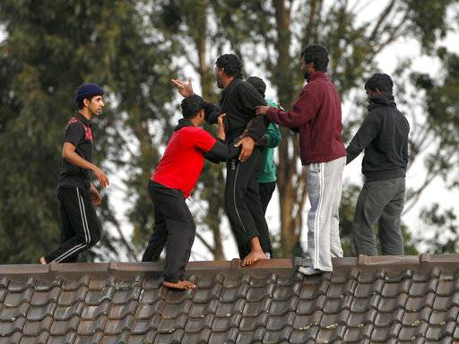 "FILE - In this Sept. 21, 2010 file photo, asylum seekers stop a fellow detainee from jumping off the Villawood Detention Center roof in Sydney, Australia, during a protest by the detainees who say they are scared of being returned to their home countries and upset over the death of a fellow detainee on the previous day. The awarding of the Sydney Peace Prize to Black Lives Matter for its work on American race issues is being hailed by local activists as a progressive step, but is also highlighting Australia's own struggles with race relations. The Sydney Peace Foundation will award its prize to Black Lives Matter for inspiring a ""bold movement for change at a time when peace is threatened by growing inequality and injustice.� Australian activists say such issues need to be addressed at home as well."