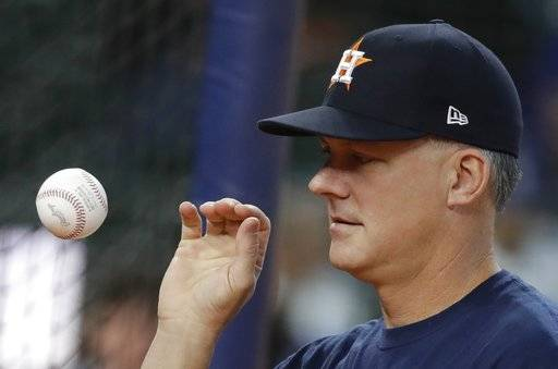 Houston Astros manager A.J. Hinch catches a ball during batting practice before Game 4 of baseball's World Series against the Los Angeles Dodgers Saturday, Oct. 28, 2017, in Houston.