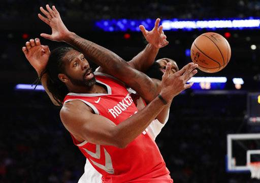 Houston Rockets' Nene Hilario, left, fights for control of the ball with New York Knicks' Kyle O'Quinn during the first half of an NBA basketball game Wednesday, Nov. 1, 2017, in New York.