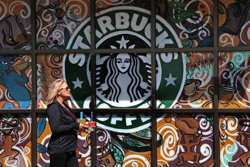 In this Tuesday, March 21, 2017, photo, a woman walks past a Starbucks coffee shop in Sewickley, Pa. Starbucks Corp. reports earnings Thursday, Nov. 2, 2017. (AP Photo/Gene J. Puskar)