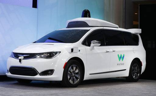 FILE - In this Sunday, Jan. 8, 2017, file photo, a Chrysler Pacifica hybrid outfitted with Waymo's suite of sensors and radar is displayed at the North American International Auto Show in Detroit. Google is partnering with AutoNation, the country's largest auto dealership chain, in its push to build a self-driving car. AutoNation said Thursday, Nov. 2, that its dealerships will provide maintenance and repairs for Waymo's self-driving fleet of Chrysler Pacifica vehicles. (AP Photo/Paul Sancya, File)