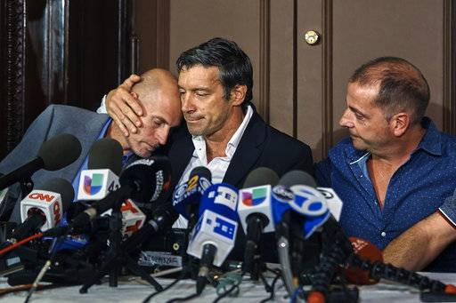 "CORRECTS NAME TO ARIEL BENVENUTO INSTEAD OF JUAN PABLO TREVISAN, RIGHT Survivors of the attack Guillermo Banchini, center, hugs Ivan Brajkovic, left, next to Ariel Benvenuto, right, during a press conference on Friday, Nov. 3, 2017, in New York. A man in a rented pickup truck mowed down pedestrians and cyclists along the busy bike path near the World Trade Center memorial on Tuesday, killing at least eight and seriously injuring others in what the mayor called ""a particularly cowardly act of terror."" (AP Photo/Andres Kudacki)"