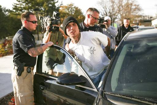 Austin Boutain, a suspect in Monday night's fatal shooting of University of Utah student ChenWei Guo, is led out of the University of Utah Department of Public Safety in Salt Lake City, Tuesday, Oct. 31, 2017. Boutain surrendered to police in Salt Lake City on Tuesday after a manhunt in the foothills near the University of Utah campus. Golden police say he's a person of interest in 63-year-old Mitchell Bradford Ingle's death. (Spenser Heaps/The Deseret News via AP)