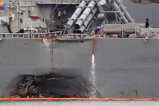 FILE - In this Aug. 22, 2017, file photo, the damaged port aft hull of the USS John S. McCain, is visible while docked at Singapore's Changi naval base in Singapore. U.S. Navy leaders are recommending a sweeping list of changes in sailor training, crew requirements and safety procedures to address systemic problems across the Pacific fleet that led to two deadly ship collisions earlier this year, killing 17 sailors. A report scheduled to be released Nov. 2, calls for about 60 recommended improvements that range from improved training on seamanship, navigation and the use of ship equipment to more basic changes to increase sleep and stress management for sailors. (AP Photo/Wong Maye-E, File)