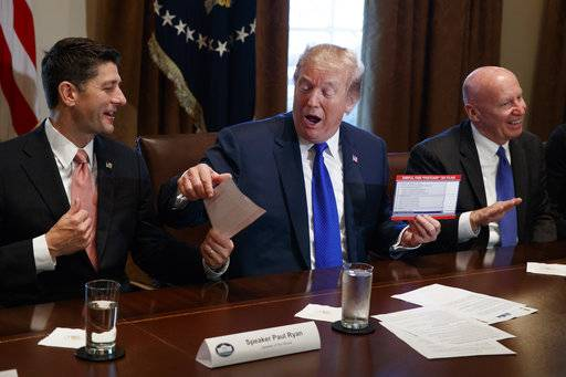 President Donald Trump holds an example of what a new tax form may look like during a meeting on tax policy with Republican lawmakers in the Cabinet Room of the White House, Thursday, Nov. 2, 2017, in Washington, with House Speaker Paul Ryan, R-Wis., and Chairman of the House Ways and Means Committee Rep. Kevin Brady, R-Texas, right. (AP Photo/Evan Vucci)
