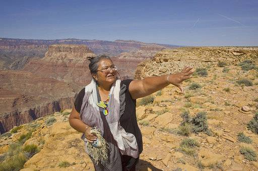 This April 7, 2015. photo provided by Tom Bean shows Renae Yellowhorse, a spokesperson for Save the Confluence, at Confluence Overlook on the East Rim of the Grand Canyon on Navajo Nation west of The Gap, Ariz., The plan for an aerial tram by the Navajo government is drawing opposition from the National Park Service, environmental groups and even some traditional Navajo herdsmen in the area. (Tom Bean via AP)