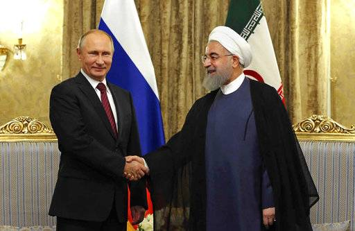 FILE - In this Wednesday, Nov. 1, 2017 file photo released by an official website of the office of the Iranian Presidency, Iran's President Hassan Rouhani, right, shakes hands with Russian President Vladimir Putin, at the Saadabad Palace in Tehran, Iran. After watching for years as the United States called the shots in the region, Russian President Vladimir Putin is seizing the reins of power in the Middle East, establishing footholds and striking alliances with unlikely partners. From Syria's battlefields to its burgeoning partnership with Iran and Turkey to its deepening ties with Saudi Arabia, Russia is stepping in to fill a void left by the United States. (Iranian Presidency Office via AP, File)