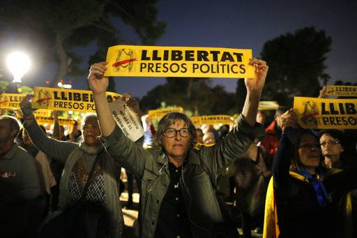 Demonstrators gather outside the Catalonian Parliament to protest against the decision of a judge to jail ex-members of the Catalan government, in Barcelona, Spain, Thursday, Nov. 2, 2017. A Spanish judge has ordered nine ex-members of the government in Catalonia jailed while they are investigated on possible charges of sedition, rebellion and embezzlement. Banners translate as 'Freedom for Political Prisoners'. (AP Photo/Manu Fernandez)