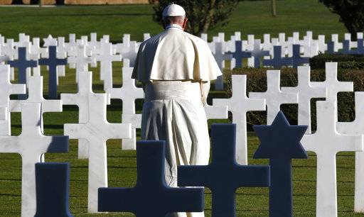 Pope Francis stands next to marble crosses at the American military cemetery in Nettuno, Italy, Thursday, Nov. 2, 2017. Pope Francis is underlining the price of war, visiting an American military cemetery and the site of a Nazi massacre in Rome. The pope will first say Mass in the Sicily-Rome American Cemetery, where 7,680 American war dead who helped liberate southern and central Italy during World War II are buried and 3,095 missing are commemorated. From there, the pope travels to the Ardeatine Caves, the site of one of the worst massacres of Nazi-occupied Rome. (Stefano Rellandini/Pool Photo via AP)