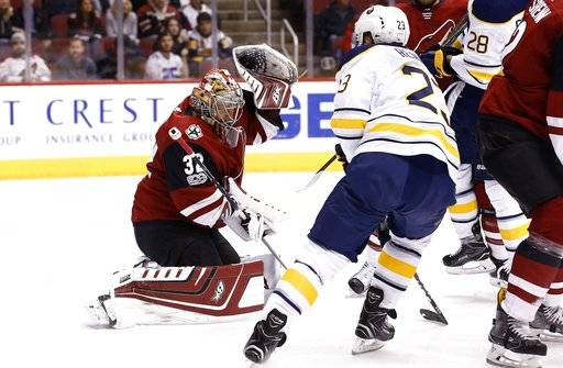 Arizona Coyotes goalie Antti Raanta (32) makes a glove save as Buffalo Sabres center Sam Reinhart (23) waits for a possible rebound during the first period of an NHL hockey game Thursday, Nov. 2, 2017, in Glendale, Ariz. (AP Photo/Ross D. Franklin)