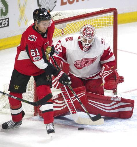 Ottawa Senators right wing Mark Stone, left, tries to deflect the puck past Detroit Red Wings goalie Jimmy Howard during third-period NHL hockey game action Thursday, Nov. 2, 2017, in Ottawa, Ontario. (Adrian Wyld/The Canadian Press via AP)