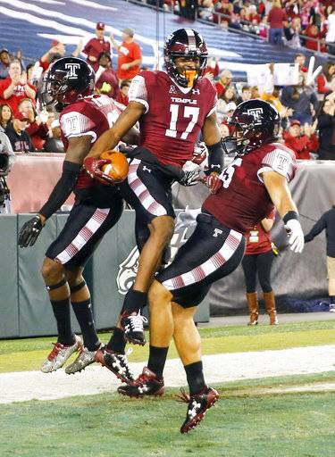 Temple wide receiver Adonis Jennings, center, celebrates his first-quarter touchdown reception against Navy with wide receiver Randle Jones, left, and fullback Rob Ritrovato during an NCAA college football game Thursday, Nov. 2, 2017, in Philadelphia. (Yong Kim/The Philadelphia Inquirer via AP)