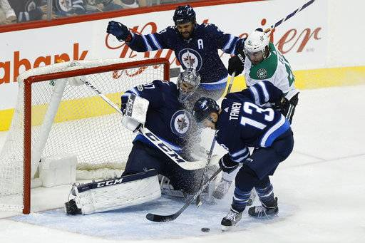 Winnipeg Jets goaltender Connor Hellebuyck (37) saves the shot from Dallas Stars' Remi Elie (40) as Jets' Dustin Byfuglien (33) and Brandon Tanev (13) defend during the second period of an NHL hockey game Thursday, Nov. 2, 2017, in Winnipeg, Manitoba. (John Woods/The Canadian Press via AP)