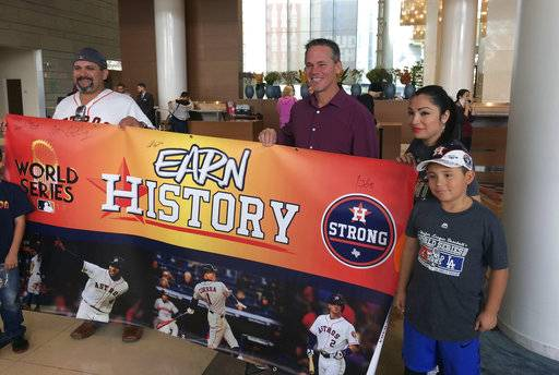Houston Astros Hall of Fame baseball player Craig Biggio, third from right, poses with Astros fans in a hotel in Los Angeles, Thursday, Nov. 2, 2017. The Astros' run to a World Series championship provided not only an emotional boost to a city recovering from Hurricane Harvey, it also gave some an economic lift.