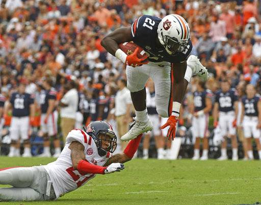 FILE - In this Oct. 7, 2017, file photo, Mississippi defensive back Javien Hamilton (21) trips up Auburn running back Kerryon Johnson (21) during the first half of an NCAA college football game in Auburn, Ala. No. 16 Auburn will face a challenging stretch run with a short-handed backfield, but Kerryon Johnson has been one of the SEC's top runners already going into the game at Texas A&M. (AP Photo/Thomas Graning, File)