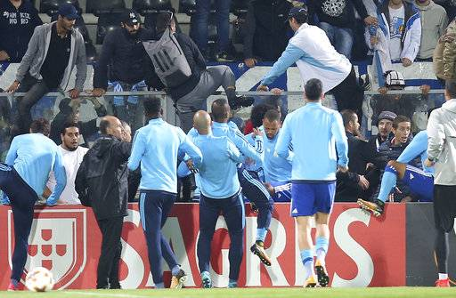 Marseille's Patrice Evra, center, back to camera is dragged away by his teammates during a scuffle with Marseille supporters who trespassed into the field before the Europa League group I soccer match between Vitoria SC and Olympique de Marseille at the D. Afonso Henriques stadium in Guimaraes, Portugal, Thursday, Nov. 2, 2017. Evra was shown a red card before the start of the match for his involvement in the incident. (AP Photo/Luis Vieira)