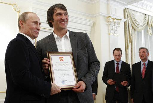 "FILE - In this May 29, 2012, file photo, Russian national ice hockey team member Alexander Ovechkin, right, holds a certficate of recognition given to him by President Vladimir Putin, left, in the Novo-Ogaryovo residence outside Moscow. Washington Capitals captain Alex Ovechkin has voiced his support for Vladimir Putin ahead of the upcoming Russian presidential elections. Ovechkin posted a message in Russian on his Instagram account Thursday, Nov. 2, 2017, announcing he's starting ""a social movement called Putin Team.� From right in the background are Russian ice hockey federation president Vladislav Tretyak and Russia's captain Ilya Nikulin. (AP Photo/Sergei Karpukhin, Pool, File)"