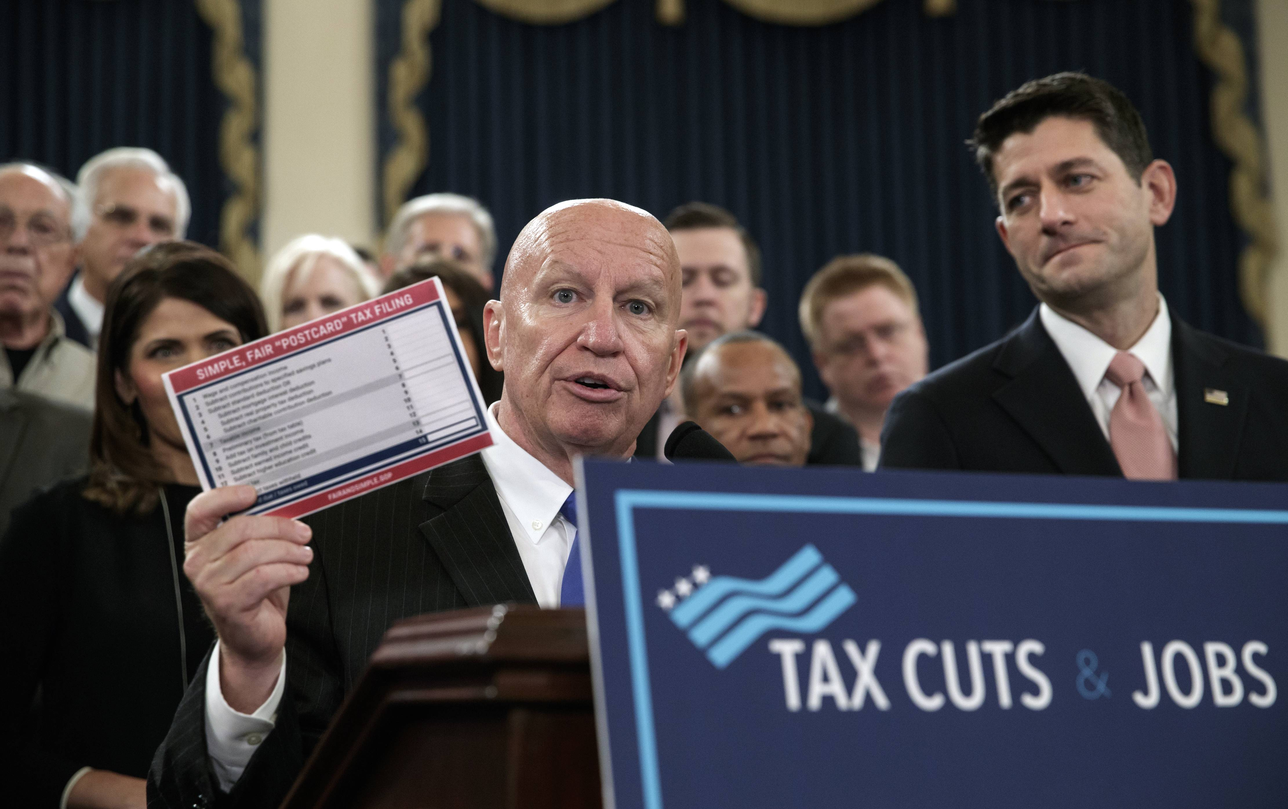 "House Ways and Means Committee Chairman Kevin Brady, a Texas Republican, joined by Speaker of the House Paul Ryan, a Wisconsin Republican, right, holds a proposed ""postcard tax filing form"" Wednesday as they unveil the GOP's far-reaching tax overhaul, the first major revamp of the tax system in three decades."
