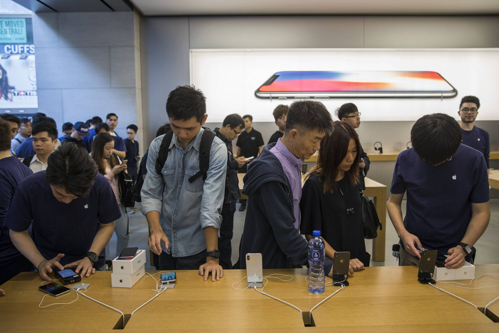 Employees assist customers purchasing the Apple iPhone X at an Apple store during its launch in Hong Kong.