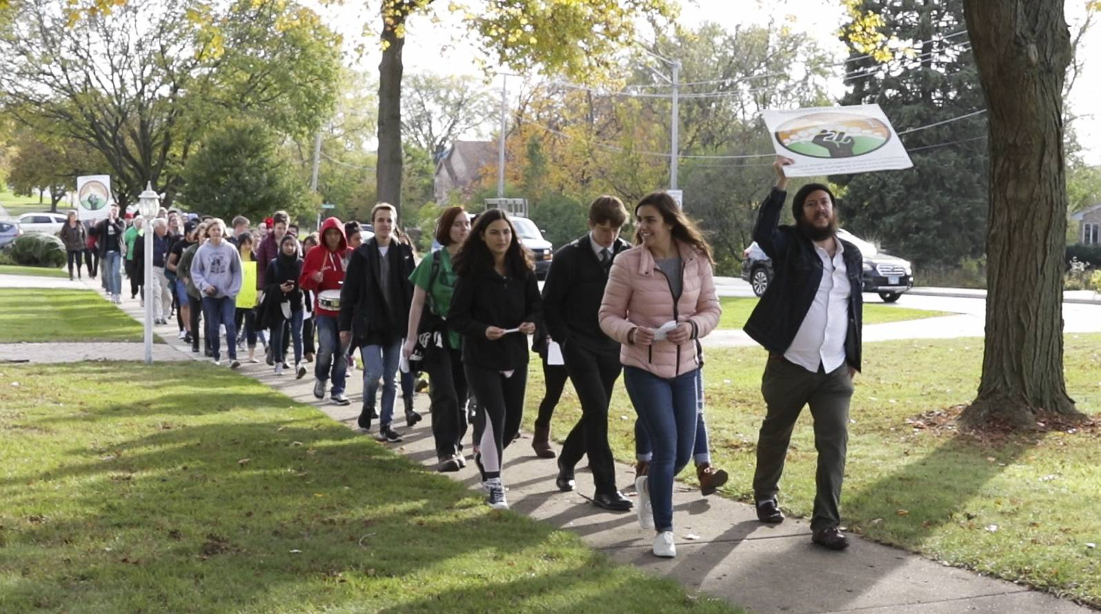 Cristóbal Cavazos with Immigrant Solidarity DuPage, right, leads the way with students from Glenbard East during a Friday march in Lombard.