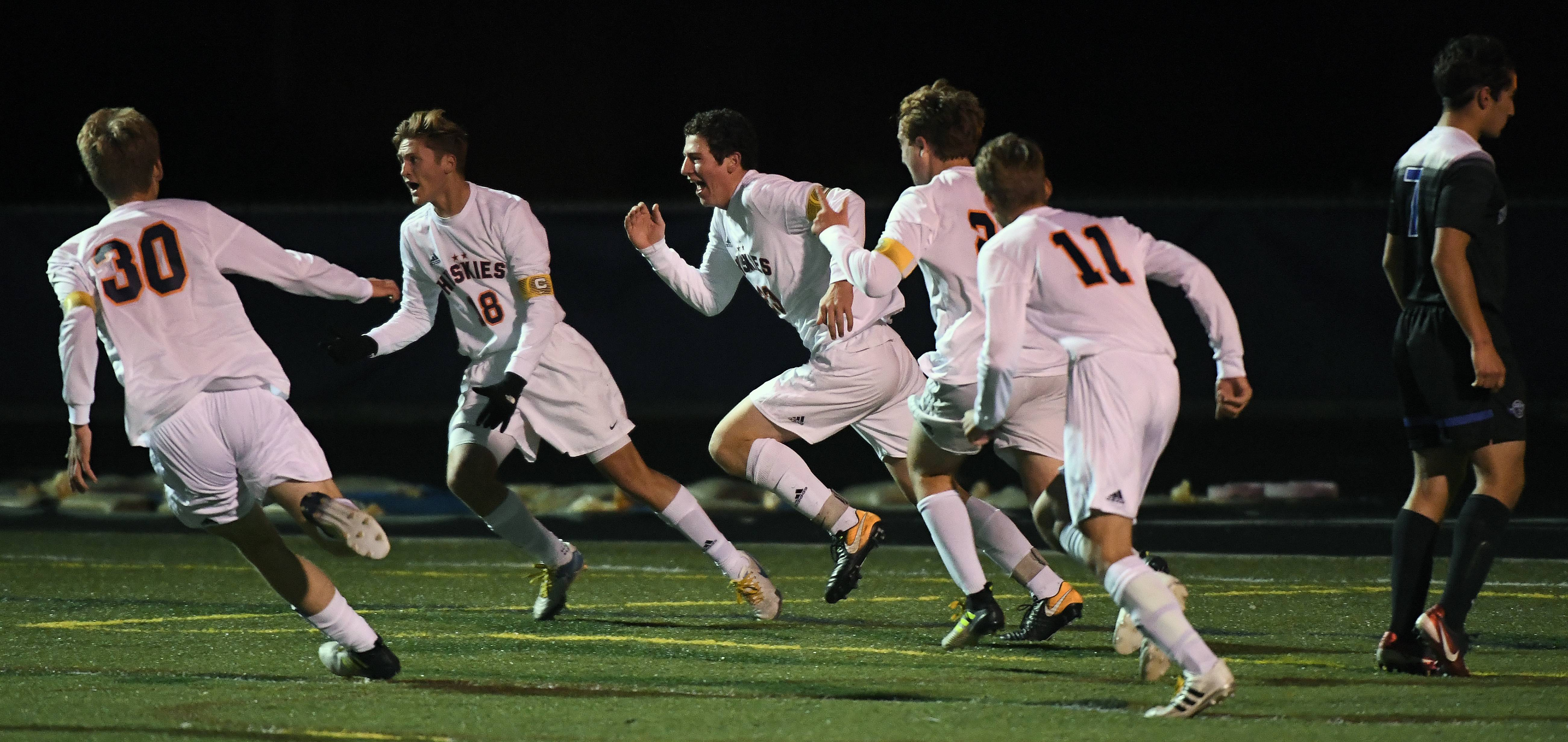Naperville North's Jack Barry, third from left, scored a first-half goal and celebrates with teammates against St. Charles North in the boys state soccer semifinals at Hoffman Estates High School on Friday.