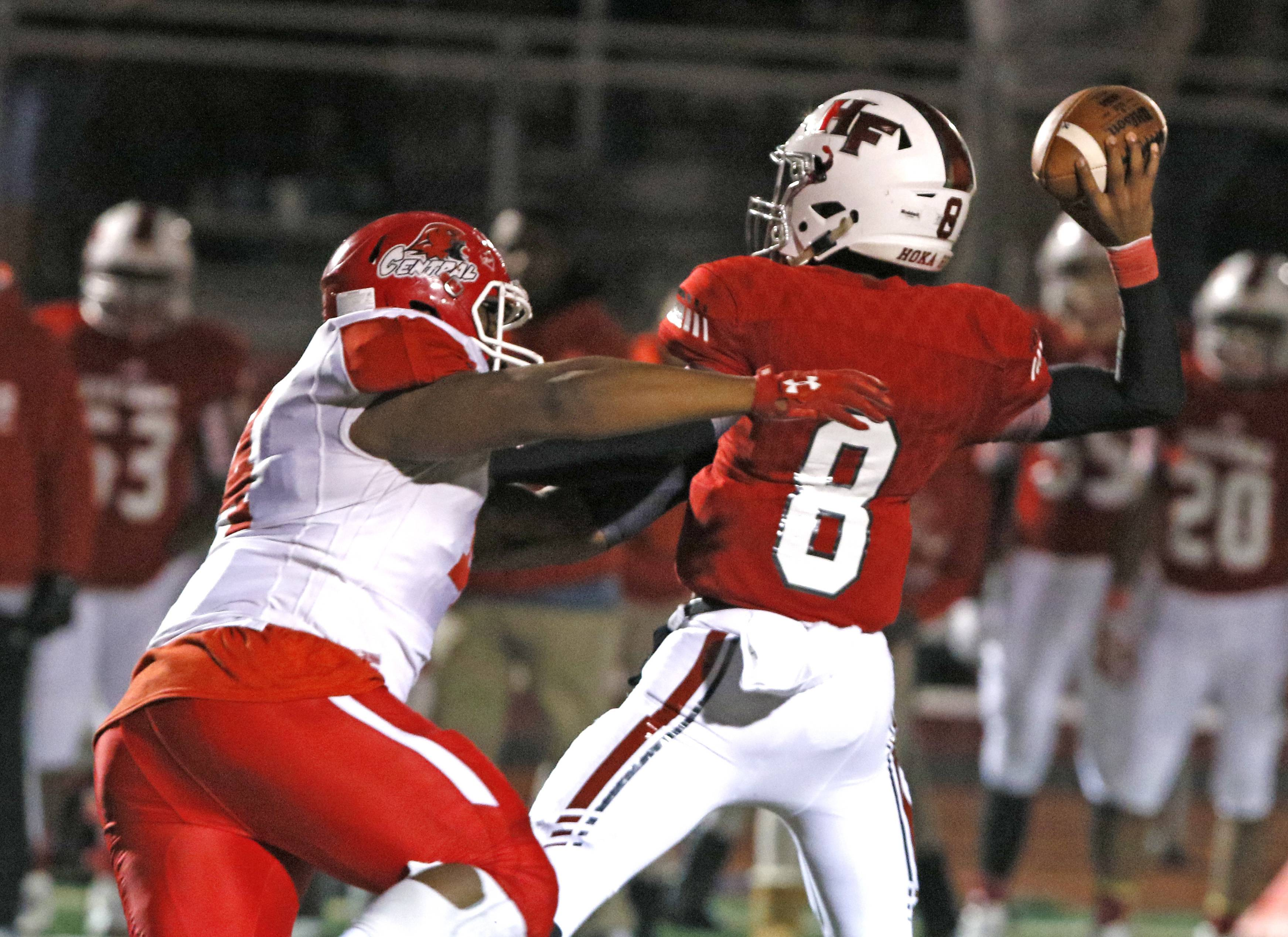 Naperville Central's Lavar Archibald, left, applies key pressure to Homewood Flossmoor's Dominick Jones (8) who throws an interception in the last minute of the fourth quarter, preserving a 31-28 win in the second round Class 8A football playoffs.