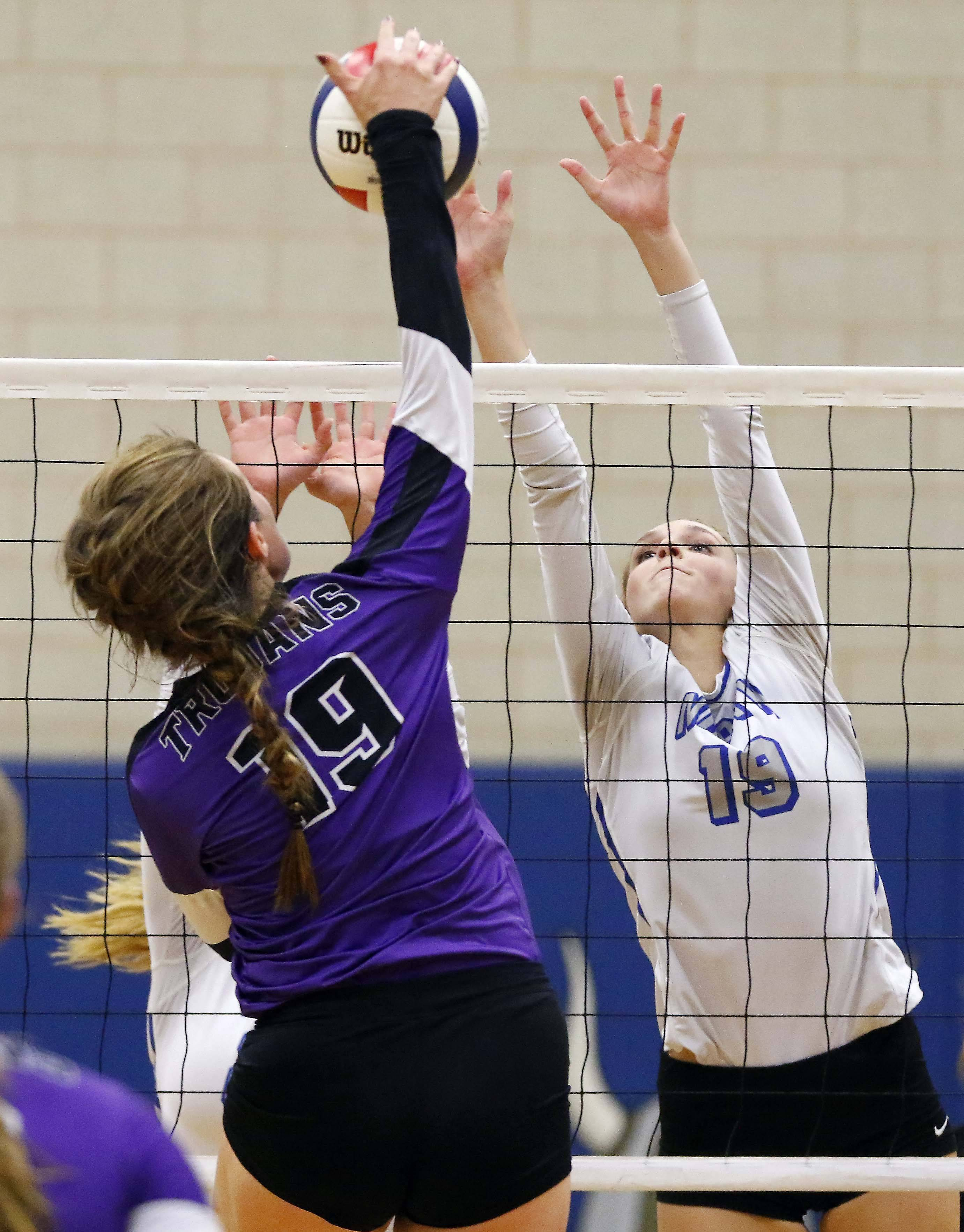 Downers Grove North's Jade Casper (19) hits the ball past St. Charles North's Abigail Graham (19) Friday in the Geneva volleyball supersectional.