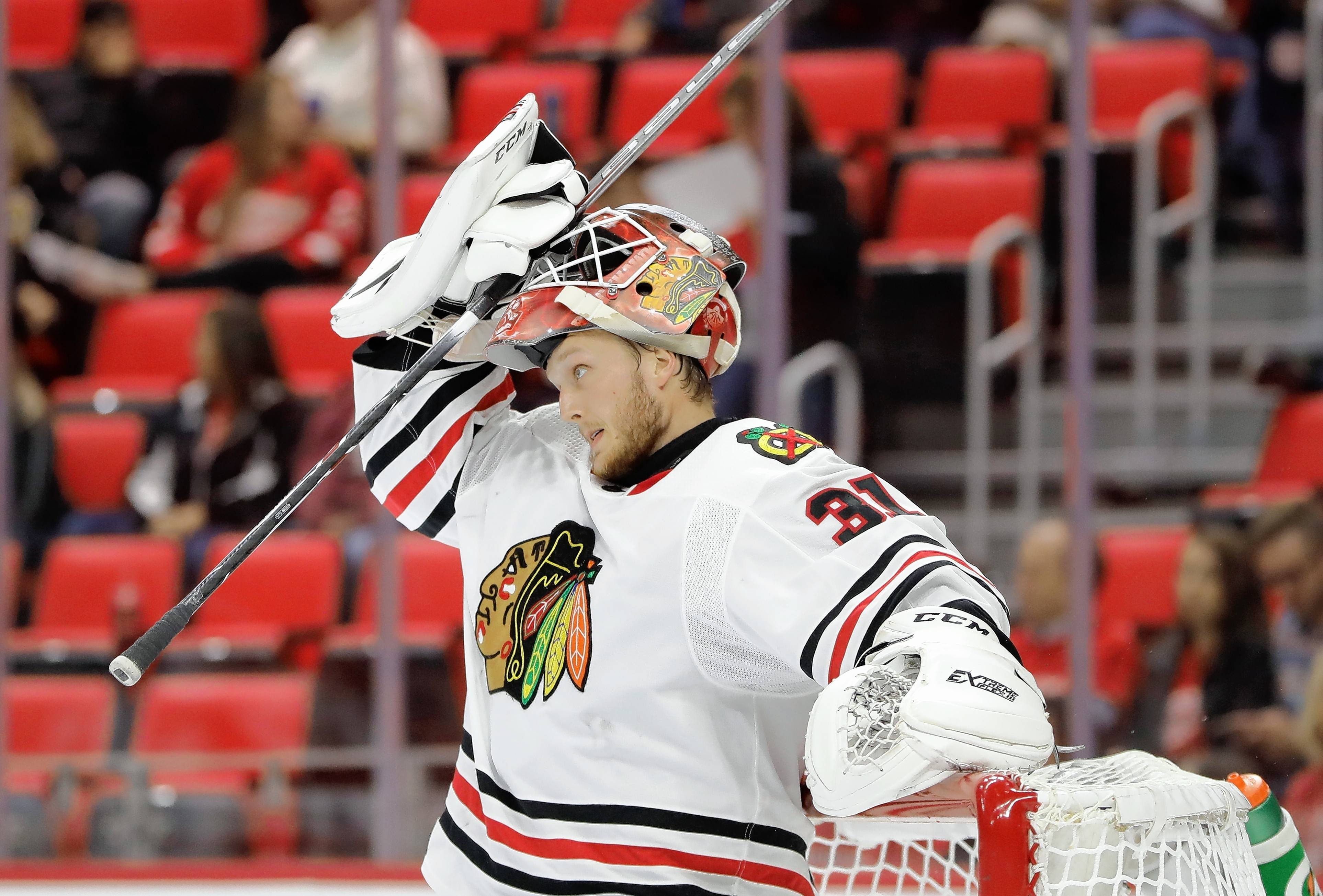 Chicago Blackhawks goalie Anton Forsberg (31) of Sweden adjusts his mask during the second period of an NHL hockey game against the Detroit Red Wings, Thursday, Sept. 28,2017, in Detroit. (AP Photo/Carlos Osorio)
