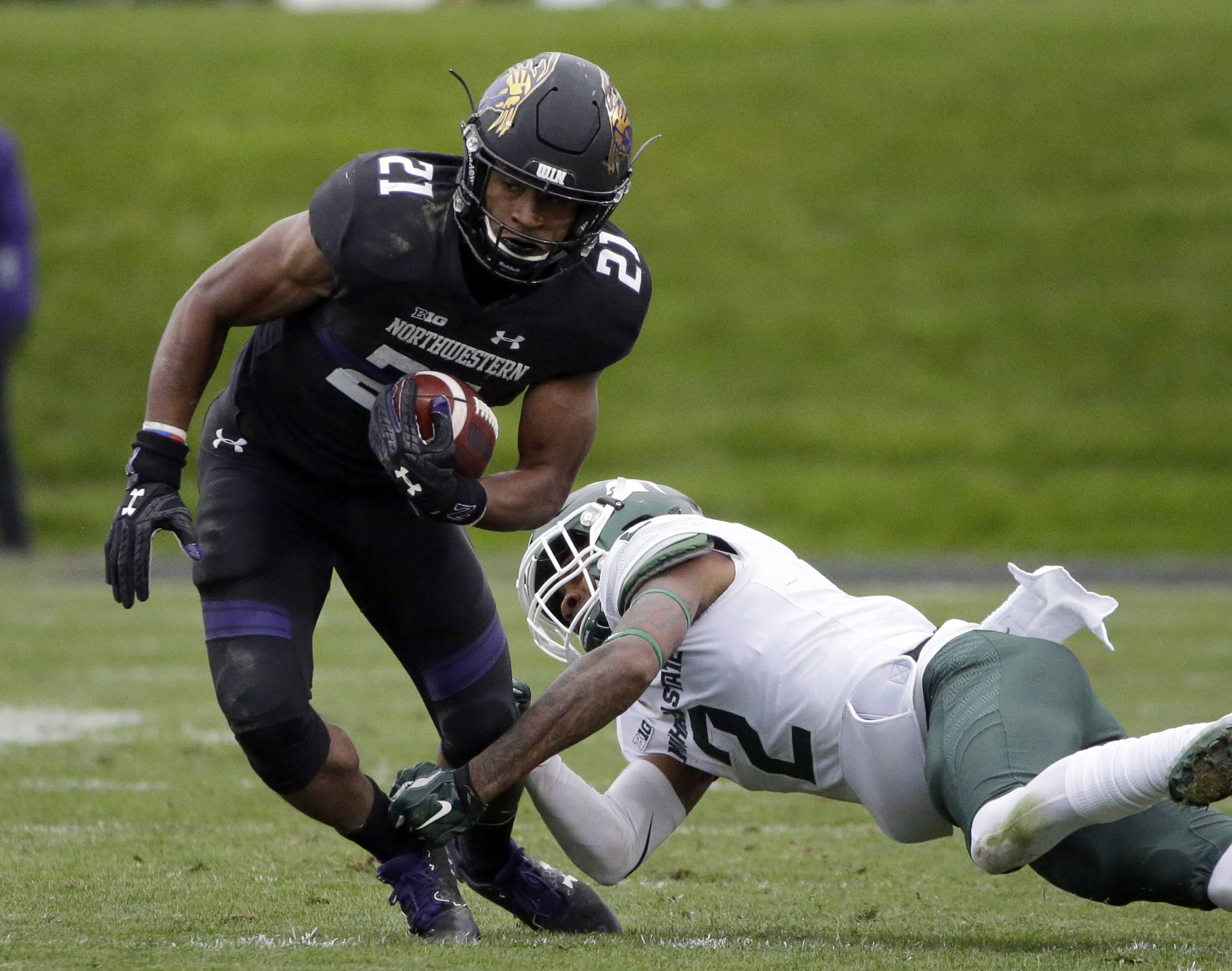 Northwestern running back Justin Jackson, left, is tackled by Michigan State cornerback Justin Layne during the first half of last week's win over Michigan State. Northwestern and Nebraska both won thrillers last week, and they could be in for another fantastic finish Saturday if this meeting is like their others at Memorial Stadium.