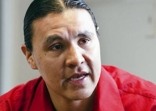 "FILE - In this Feb. 6, 2014, file photo, Chase Iron Eyes, an attorney and American Indian activist on the Standing Rock Reservation, speaks in Fort Yates, N.D. The trial for Iron Eyes, accused of inciting a riot during protests in North Dakota against the Dakota Access pipeline will likely be delayed. Attorneys for Iron Eyes said Friday, Nov. 3, 2017, they want to gather more evidence for their effort to present a ""necessity"" defense, arguing a crime was justified because it prevented a greater harm. (AP Photo/Kevin Cederstrom, File)"