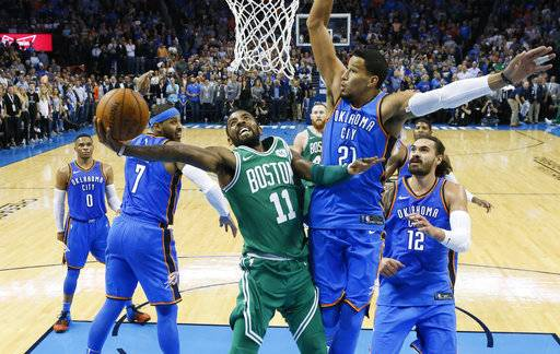 Boston Celtics guard Kyrie Irving (11) shoots between Oklahoma City Thunder forward Carmelo Anthony (7) and guard Andre Roberson (21) in the second quarter of an NBA basketball game in Oklahoma City, Friday, Nov. 3, 2017. (AP Photo/Sue Ogrocki)