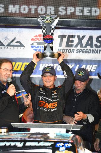 Johnny Sauter holds up the trophy in Victory Lane after the NASCAR Truck Series auto race at Texas Motor Speedway in Fort Worth, Texas, Friday, Nov. 3, 2017. (AP Photo/Larry Papke)