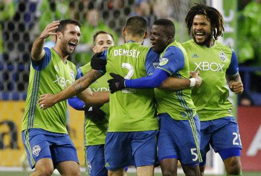 Seattle Sounders forward Clint Dempsey (2) is greeted by teammates after he scored the first of two goals in the second half of the second leg of an MLS soccer Western Conference semifinal against the Vancouver Whitecaps, Thursday, Nov. 2, 2017, in Seattle. The Sounders won 2-0 and advanced to the Western Conference championship series. (AP Photo/Ted S. Warren)